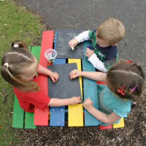 An overhead photograph of three children playing with chalkboards on a colourful picnic table