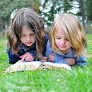 A photograph of two children lying down in the grass reading a bible